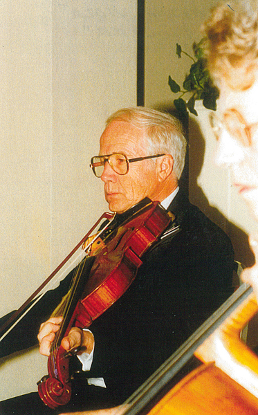 A recent photo of Don Mildrum '53 playing the viola at a company office opening