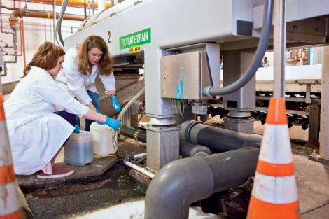 two college students retreive waste water from filtration system