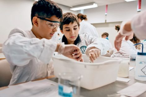two students in lab coats experiment with wastewater in small basin