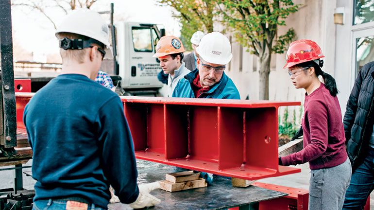 students and professors unload large red I-beam