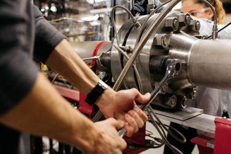 student fastens bolt on pressure tube